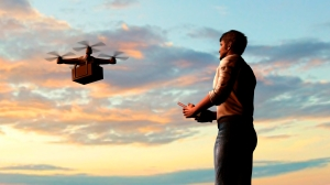 man operating of flying drone quadrocopter with package at the sky